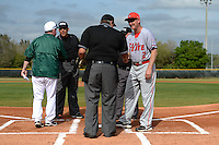 Dartmouth Big Green head coach Bob Whalen and Rich Maloney (2) exchange lineup cards with umpires Kyle Reese, Jerry Fowler and Clark Husky before a game against the Ball State Cardinals on March 7, 2015 at North Charlotte Regional Park in Port Charlotte, Florida.  Ball State defeated Dartmouth 7-4.  (Mike Janes/Four Seam Images)