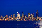 View of downtown Seattle taken from Harbor Avenue, across Elliott Bay just at sunset.  Full moon reflects on bay.