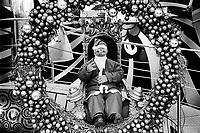 France. Ile-de-France Department. Paris. Avenue des Champs-Élysées. A seated dwarf is dressed as Santa Claus. Christmas wreath with balls. 20.11.13 © 2013 Didier Ruef