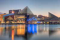 The National Aquarium, Baltimore reflects off the waters of the Inner Harbor during the last hour before sunrise in Baltimore, Maryland.