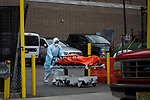 A healthcare worker wheels the body of a COVID-19 victim to a refrigerated trailer used as a temporary morgue outside of Wyckoff Heights Medical Center in the Brooklyn borough of New York City on April 5, 2020.  Photograph by Michael Nagle