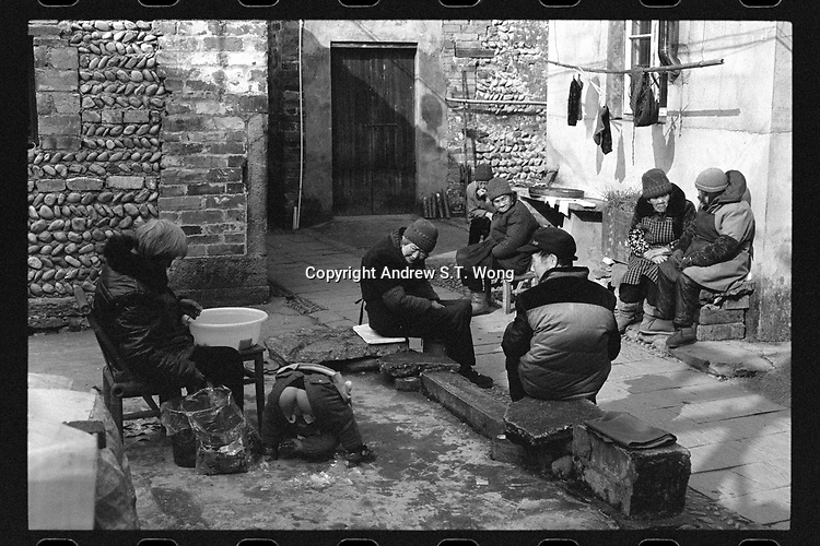 Xiashan Village, Kaihua County, Quzhou City, Zhejiang Province - Elderly villagers chat and watch a toddler play, December 2020. Xiashan Village is located along the Qiantang River.