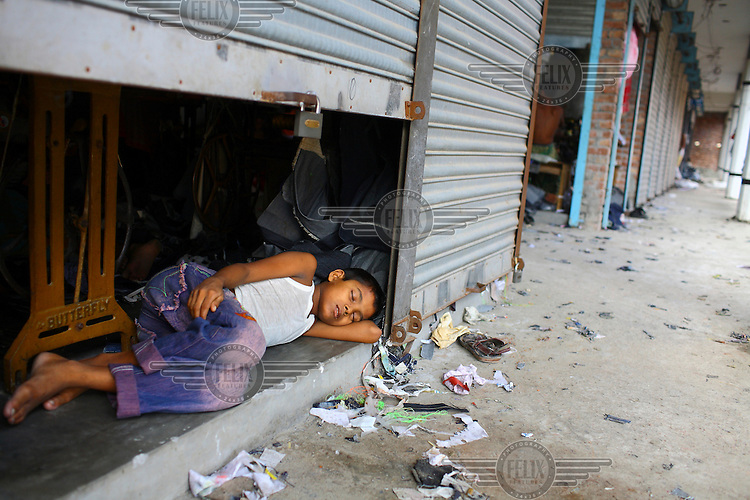 A young man working in a garment factory sleeps by an open shutter at the front of the premises.