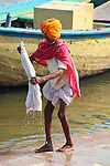 The Ganges River has many uses for locals and pilgrims. Here a man washes his shirt in the holy waters.