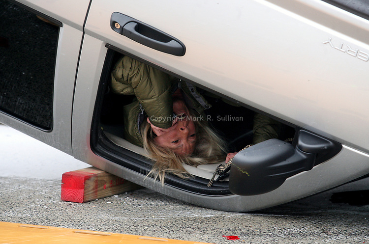East Brunswick police and fire fighters responded to an overturned SUV on the overpass of the New Jersey Turnpike along Hardenburg Lane in East Brunswick on Thursday Jan. 28, 2010.<br />  Here a women hangs upside down inside the overturned vehicle while talking on a cell phone as she awaits rescue from the vehicle.<br />  Icy roads caused a number of car crashes in  the Central New Jersey area.<br /> <br /> (AP PHOTO/HOME NEWS TRIBUNE/MARK R. SULLIVAN)