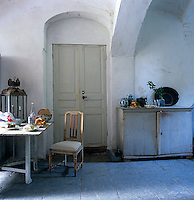 An antique gate-legged wooden table provides a place for a simple lunch in the vaulted kitchen