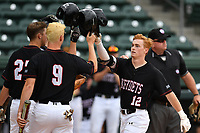 Designated hitter Matt Dunlevy (12) of the VMI Keydets is congratulated by Josh Hollifield (27) and Jake Huggins (9) after hitting a home run in a game against the Mercer Bears as part of the Southern Conference Championship series on Wednesday, May 24, 2017, at Fluor Field at the West End in Greenville, South Carolina. Mercer won, 11-6. (Tom Priddy/Four Seam Images)