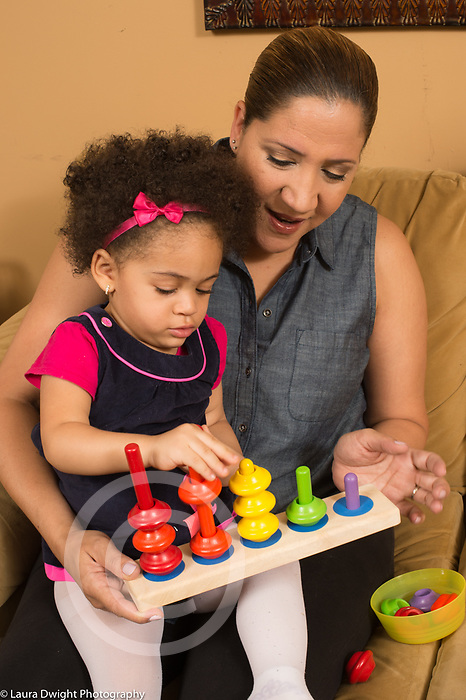 Grandmother and 21 month old toddler granddaughter sitting on couch together, helping her play with new peg and color matching spindle toy