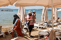Saad (right), and their son, from east London, UK walk on the beach at the Wome Deluxe hotel, one of many hotels on Turkey's southern coastline, catering to the halal tourism market.  The Women Deluxe opened as an Islamic friendly hotel in 2015.