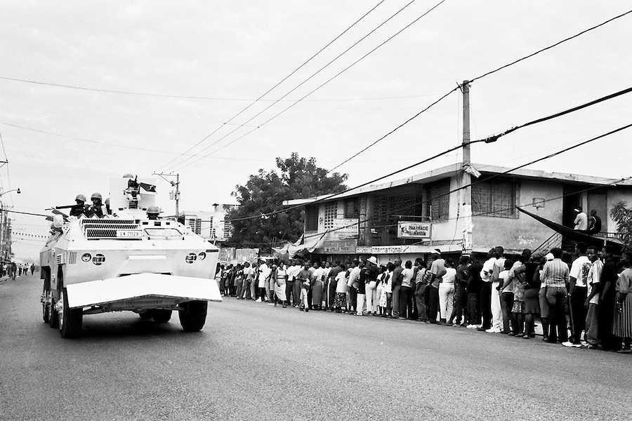 UN patrol driving past Haitians waiting in line to vote on election day.