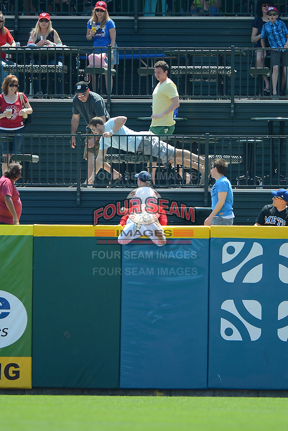 Buffalo Bisons outfielder Moises Sierra #14 hangs over the top of the outfield wall after attempting to catch a home run by Blake Tekotte #2 (not shown) as fans scramble for the ball during a game against the Charlotte Knights on May 19, 2013 at Coca-Cola Field in Buffalo, New York.  Buffalo defeated Charlotte 11-6.  (Mike Janes/Four Seam Images)