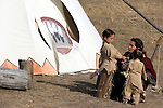 A young Native American Indian family by the tipi.  A mom and her son on the left and baby girl on the right