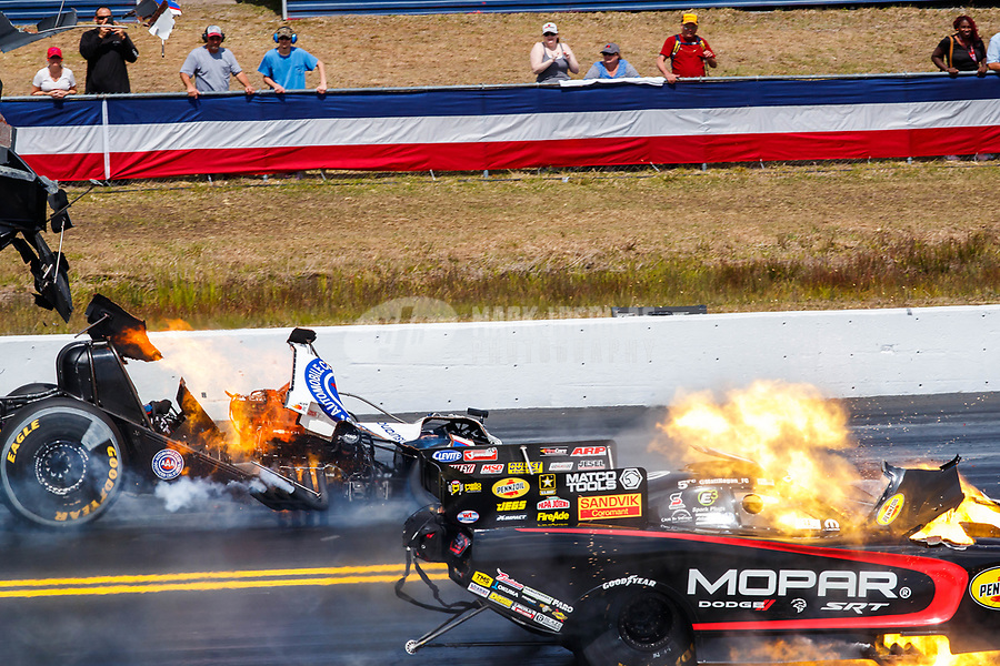 Mar 18, 2018; Gainesville, FL, USA; NHRA funny car driver Robert Hight (left) explodes the engine of his car launching the carbon fiber body as opponent Matt Hagan also suffers an engine explosion during the Gatornationals at Gainesville Raceway. Both drivers would be uninjured. Mandatory Credit: Mark J. Rebilas-USA TODAY Sports