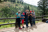 People look at a petrified tree in the Roosevelt-Tower area of Yellowstone National Park, Wyoming, USA. The stump is a few meters tall and is the remains of a 50-million-year-old Redwood tree, a species that doesn't grow in the area now. The stump is behind a tall fence. Decades ago, there were three stumps in the area, but souvenir hunters removed the other two.