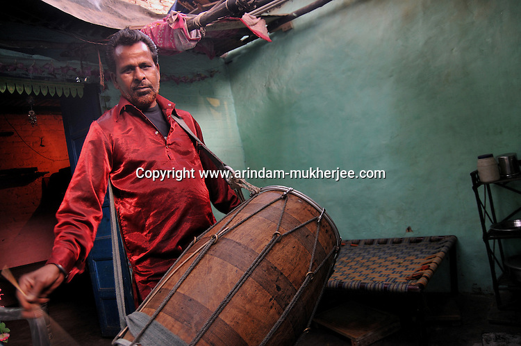 Leela Keshar is a Dhol performer staying at Katputly colony in New Delhi, India. he generally performs in Marrige cerimonies and folk art festivals through out the country and also once visited Dubai to perform. New Delhi, India, 16.11.09 Kathputly colony is a slum area in West Delhi. This slum seems like any other slum areas of modern India with dysfunctional electricity, non existing sanitation and poverty. As a part of Delhi, this is also ailed with water crisis. Large families live their lives crammed together in a single room with all the odds which complement poverty. One thing which differentiates this slum with any other is the people living in the colony. Nearly everybody in this slum is a traditional performing artist; and they have been migrating to this area for last 50 years from different parts of the country for a better livelihood. They are magicians, acrobats, jugglers, puppeteers, dancers and musicians. These artistes perform in star rated hotels, marriage ceremonies of the richer section, functions, and festivities all around the country and the world. Most of the artisans I met here, have performed in Europe and America but such opportunities are rare to come by. They struggle to keep their art form alive. They say that they don't get any help or support from the government for their basic needs and for the well being of the Kathputly colony -  though they have uphold the prestige of the country internationally. Polluted air, dirty alleys smelling of urine, colourful dress and sound of music characterise Kathputly colony, which is the one of its kind in India. Arindam Mukherjee