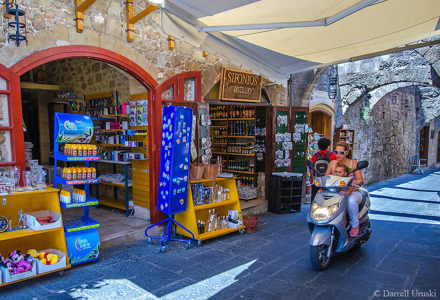 Urban Street Photograph of a lady with young girl driving her scooter through the market place in the city of Rhodes, Greece.