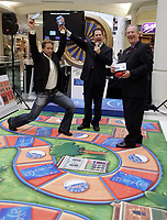 Victor Kraatz (left), 10-time Canadian Ice Dance Pairs Champion, celebrates his win against BMO Bank of Montreal's Garry Greene (right), in the BMO Debit Dash board game to publicize BMO customers can now earn AIR MILES reward miles with their BMO Bank of Montreal debit card. Emcee Michael Robinson demonstrated the benefits of Canada's most comprehensive debit card rewards program to shoppers at Metropolis Mall in Burnaby, B.C., Thursday June 14, 2007. (CNW Group/BMO Bank of Montreal)