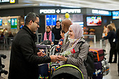 A family is united as passengers arrive from Dubai after a 14-hour flight on Emirates flight 231, at the international terminal at Dulles International Airport in Dulles, Va., Monday, March16, 2020. Some people are taking the precaution of wearing face masks as they arrive to be greeted by family and or friends. Credit: Rod Lamkey / CNP
