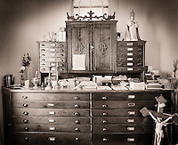 The bureau of a priest with many drawers for vestments and other attire, adorned with religious iconery.