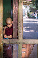 A young novice monk plays with a toy car in the window at Kalaywa Taw Ya Monastery, Yangon, Myanmar