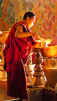 A young buddhist monk tends to butter candles inside Tashilhunpo monastary in Shigatse, Tibet