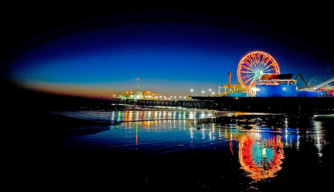 The ferris wheel at the Santa Monica Pier is reflected in the water along the beach at Santa Monica, California