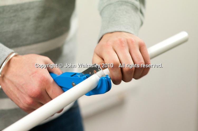 Student electrician cutting plastioc tubing to length, Able Skills, Dartford, Kent.