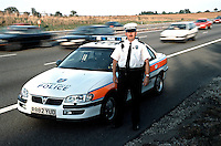 Traffic police officer stood next to his police rapid response traffic vehicle on the hardshoulder of the motorway.