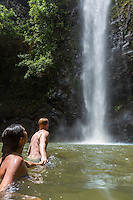 A young couple go for a dip in the water at Uluwehi Falls, Kaua'i.
