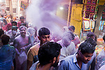 A man throws gulal (dry colour powder) to others on the occassion of Holi Festival in India. Holi - The  Hindu festival of colour is celibrated for a week in the Brraj region of Uttar Pradesh, India.