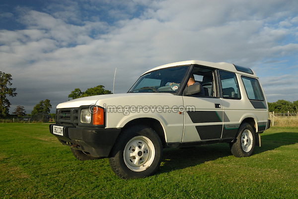 One of the very first Land Rover Discovery 1 speeding along a field in Surrey, south England. Europe, UK, England, Surrey, Dunsfold. --- No releases available. Automotive trademarks are the property of the trademark holder, authorization may be needed for some uses.