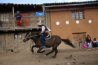 A man rides on a horse during Yawar Fiesta celebrations in his community in the Peruvian Andes.
