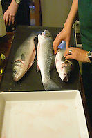 How to prepare fish baked in the oven in salt crust (en croute de sel), recipe, series of pictures: three fish on the preparation table cleaned and ready to be prepared with salt, a man holding the fish Clos des Iles Le Brusc Six Fours Cote d'Azur Var France