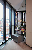In the guest room a dressing table and pouffe is placed in the corner next to the floor-to-ceiling windows.