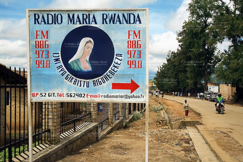 Rwanda. Southern province. Gitarama. District of Muhanga. Advertisement for FM Radio Maria Rwanda. Catholic radio broadcast program. Drawing of the Virgin Mary. Red arrow. A motorbike on the concrete road. © 2007 Didier Ruef