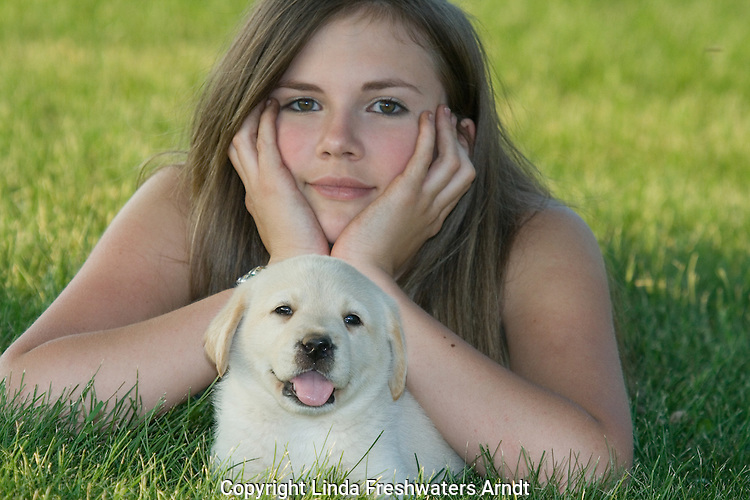 Teenage girl lying in the grass with a Yellow Labrador retriever (AKC) puppy
