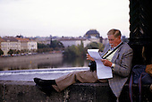 Prague, Czech Republic. Man in a sports jacket reading a piece of paper on Charles Bridge.
