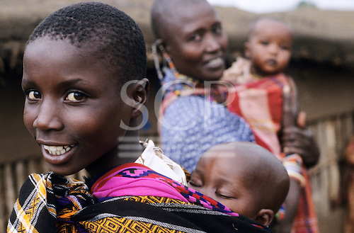 Lolgorian, Kenya. Young African woman with her baby asleep in a cotton wrap sling on her back.