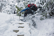 Hiker climbing snow covered trail ladders along the Willey Range Trail in the White Mountains, New Hampshire during the winter months.