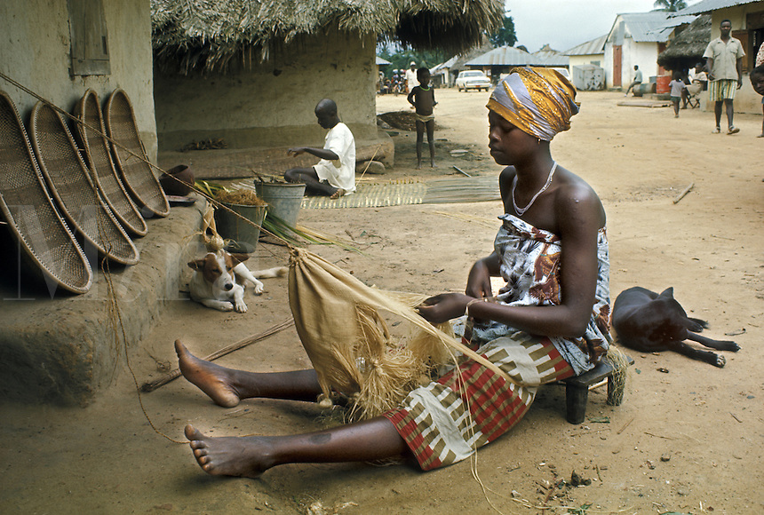 West Africa, Liberia, Kpelle tribe: young woman weaving a bag from raphia palm fiber in village.