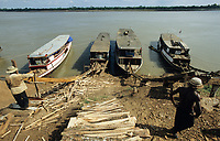 CAMBODIA, Mekong river, Kratie, logging of forest, loading the timber on Mekong river boats by sliding ramp