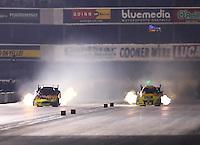 Nov 12, 2016; Pomona, CA, USA; NHRA funny car driver Jim Campbell (left) races alongside Bob Bode during qualifying for the Auto Club Finals at Auto Club Raceway at Pomona. Mandatory Credit: Mark J. Rebilas-USA TODAY Sports