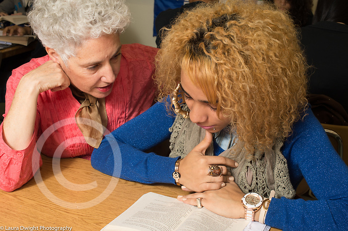Education High School female teacher talking one to one in classroom
