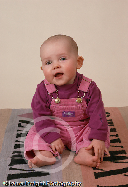 portrait of 6 month old sitting baby girl vertical Caucasian