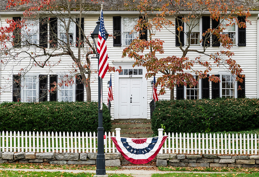 Charming colonial house with patriotic American flag.