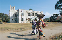 TANZANIA Bagamoyo, women infront of old german fort Boma in Bagamoyo which was from 188-1891 the capital of former german colony east africa and the dhow harbour for the slave and ivory trade to Zanzibar / TANSANIA, Bagamoyo, Frauen vor alter deutscher Festung Boma in Bagamoyo der Verwaltungshaupstadt der ehemaligen deutschen Kolonie Ostafrika 1887 bis 1891, Bagamoyo war einst Dhau Hafen und Umschlagplatz fuer Elfenbein und Sklaven nach Sansibar