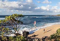 A windsurfer makes his way to shore while a woman leaves a trail of footprints across the sand at Ho'okipa Beach on Maui.