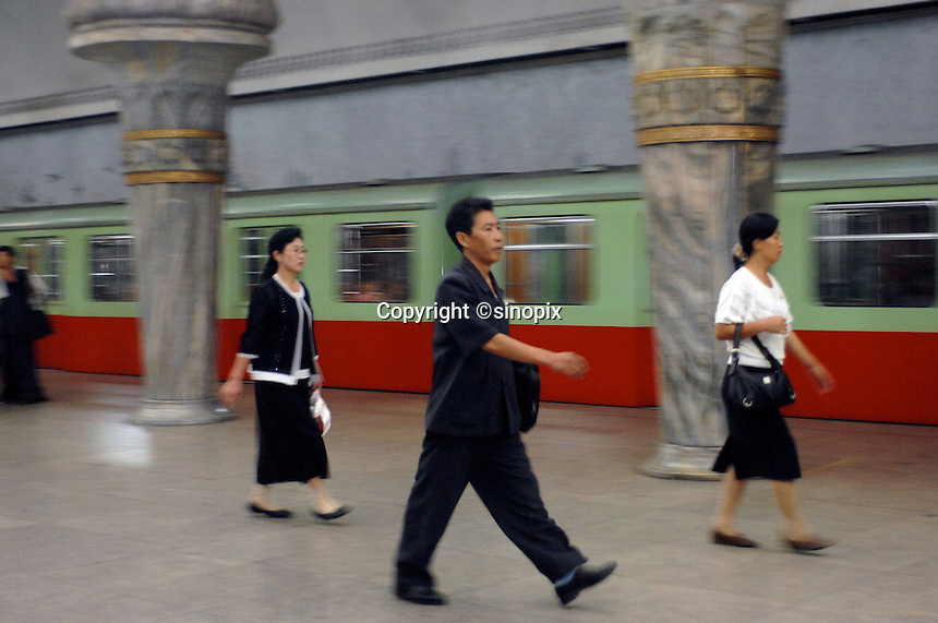 "Commuters in the Pyongyang Metro station in North Korea. The DPRK (Democratic People's Republic of Korea) is the last great dictatorship where the people are bombarded with images of the ""Eternal President"" Kim Il-sung who died in 1994 and his son and current leader Kim Jong-il who are worshipped like a God."