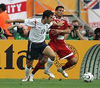 JUNE 15, 2006: Nuremberg, Germany: English midfielder (11) Joe Cole tries to make it around Trinidad & Tobago midfielder (11) Carlos Edwards. England defeated Trinidad & Tobago, 2-0, in their FIFA World Cup Group B match at Franken-Stadion.