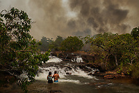 Tourists observe a fire outbreak while bathing in the waters of the Mutum River, in the rural area of Santo Antonio Leverger, in the Pantanal of Mato Grosso.